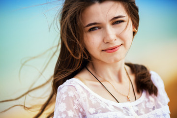 Portrait of attractive woman standing at beach.