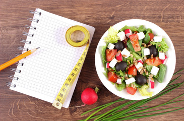 Fresh greek salad with vegetables, centimeter and notepad for writing notes, healthy nutrition and slimming concept