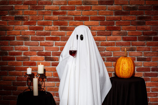 Ghost holding wine over brick background. Halloween party.