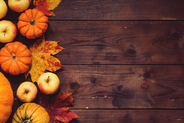 Thanksgiving background: Apples, pumpkins and fallen leaves on wooden background. Copy space for text. Halloween, Thanksgiving day or seasonal background. Design mock up.