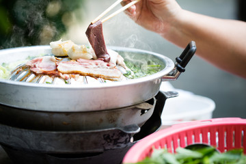 Grilling sliced pork and meat on hot pan asian style / selectiv