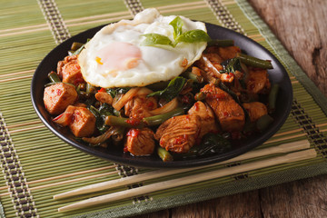 Spicy Stir-Fry Chicken with basil, green beans and a fried egg close-up horizontal