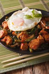 Thai cuisine: Stir-Fry Gai Pad Krapow chicken on a plate close-up vertical