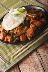 Thai cuisine chicken with basil, green beans and a fried egg close-up vertical