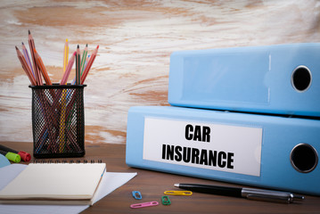 Car Insurance, Office Binder on Wooden Desk. On the table colore