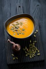 Pumpkin cream-soup in a bowl on a black wooden serving board