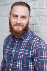 portrait of a young bearded man in a flannel shirt