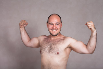 Happy shirtless man posing and showing his strong body