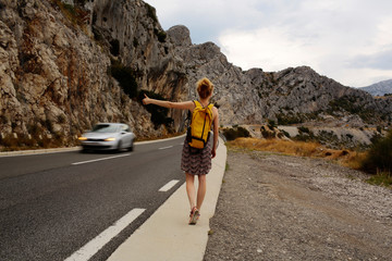 Girl hitchhiking with thumb up