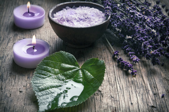 Wellness concept with lavender, a green leaf, candles and bowl of salt in old style coloring