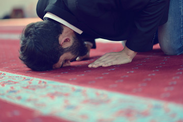 Younger Muslim man praying