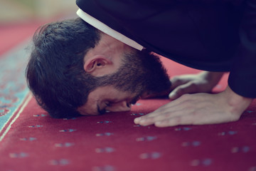 Younger Muslim man praying