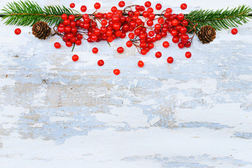 Winter Background - White Snowy Wooden Texture with Red Berry Branches and Pinecones - Christmas Forest - top view, horizontal border