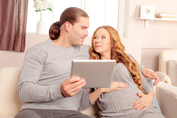 Happy family couple and digital technology. Young pregnant caucasian woman with her husband holding tablet pc on sofa at home.