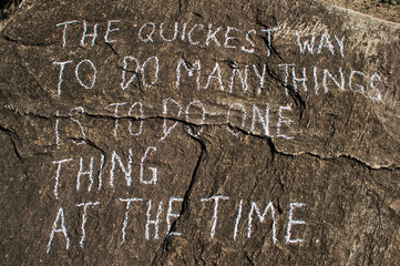 The quickest way to do many things is to do one thing at the time. Creative motivation concept is written on a stone.
