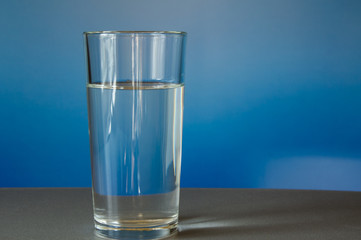 glass of water is on the table, blue background