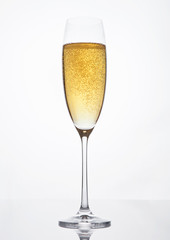 Glass of sparkling champagne with bubbles on white