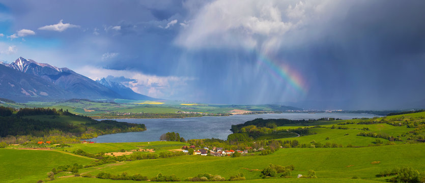 Rain and rainbow over small village