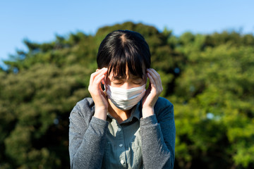 頭を押さえるマスクの女性