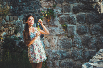 Portrait of young romantic woman with long hair, red lips and manicure in white dress flowers. Attractive girl in Stari Bar old fortress, Montenegro. Brunette female walks around castle, the magic
