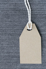 Brown paper label with hemp rope tied on denim or jeans.