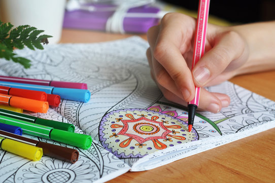Coloring an adult coloring book