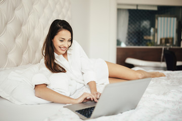 Beatufiul brunette using laptop in bed