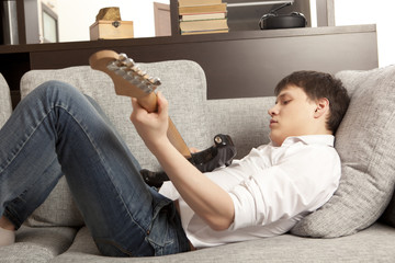 Young man with electric guitar on sofa