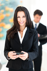 Businesswoman texting with mobile phone in hotel office lobby