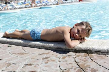 Child lying on edge of pool