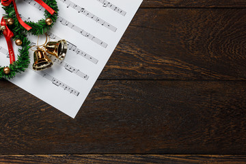 Top view Christmas music note paper  with Christmas wreath on wooden.