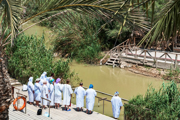 group of pilgrims going baptize at river jordan, israel