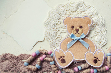 Decorative photo collage in vintage style with teddy bear and textile elements.
