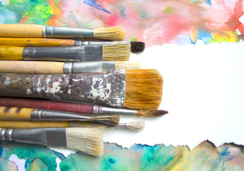 Paintbrushes on abstract colorful watercolor background with place for text. Blank for motivating quote, note, message.