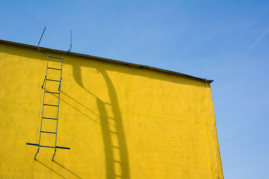 Top of yellow wall. Ladder to the roof. Strong shadow on the facade. Blue sky.