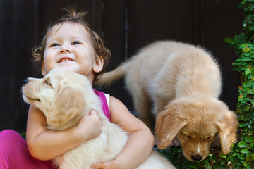 Funny photo of happy baby girl hug beautiful golden labrador retriever puppy, play together. Family lifestyle, training dogs. Positive emotions of children fun games with home pet on summer vacation.