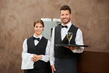 Kellner und Kellnerin servieren Weißwein