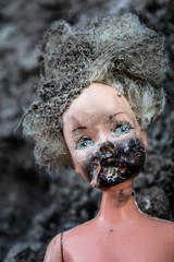 Melted scary girl doll on a ash background