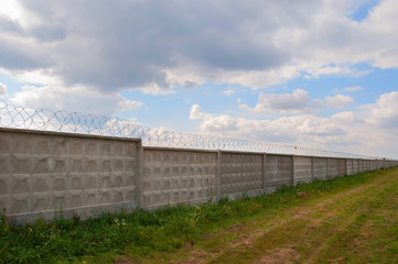 Wall with barbed wire on a background of blue sky. long fence