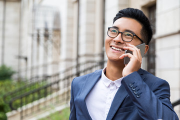 Asian man in glasses on the phone