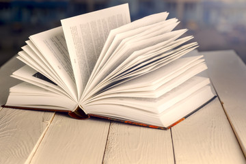 Open book on wood planks over abstract light background