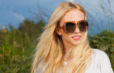 Fashionable beautiful young blonde woman in vintage sunglasses her hair streamed in the breeze on a warm summer evening. Relax.