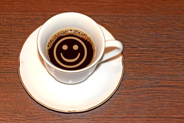 Cup of coffee and a smiley face . The concept of morning good mood .
