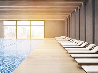 Sunlit public pool with chaise longues