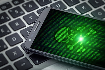 skull of death on smartphone screen. Hacked mobile phone on laptop computer