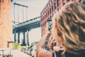 Woman taking picture of Manhattan Bridge