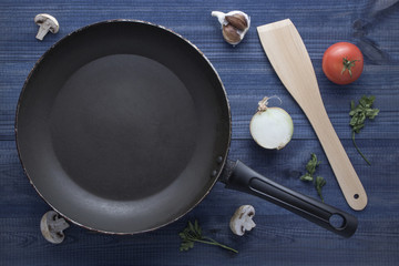 empty pan with mushrooms , tomato, garlic, onion, parsley leaves and wooden spatula on blue wooden table.