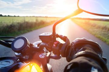 Motorrad fahren auf Landstrasse im Sonnenuntergang bei blauem Himmel