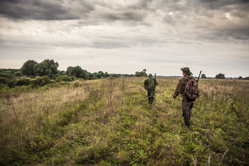 Hunters going through rural field with dramatic sky during hunting season