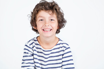Close up portrait of happy cute little boy with curly hair